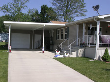 Carport covering driveway leading to side entrance of a home